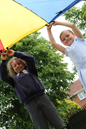 2 pupils playing with a large kite