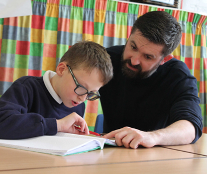 A pupil working with the help from a teacher