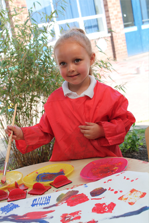 A young pupil painting outside