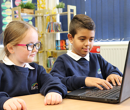 2 pupils working on a laptop together